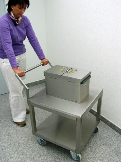 A woman using a lead-shielded laboratory trolley